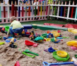 Sandkasten mit viel Spielzeug